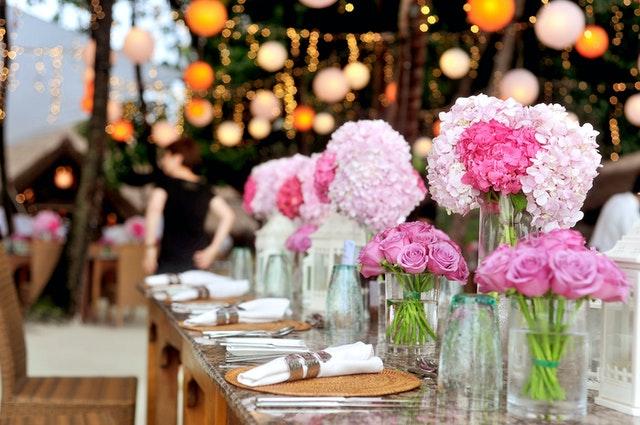 różowe kwiaty i zastawa na stole weselnym