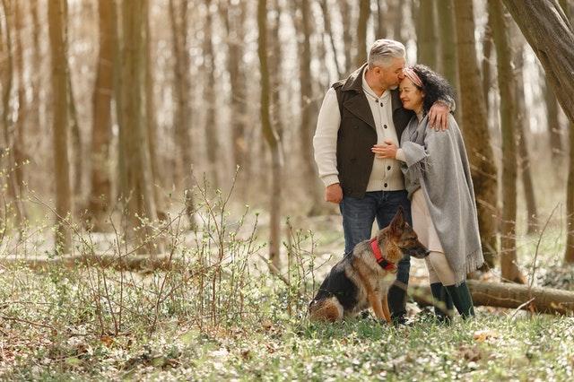 starsza para wtulona w siebie na spacerze w lesie z psem