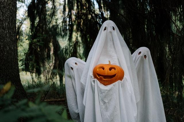 dzieci przebrane za duchy mają na sobie prześcieradło i trzymają dynię