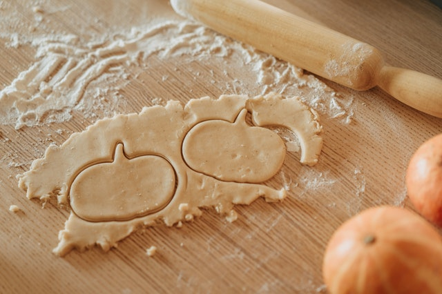 ciasto, które ktoś formuje w kształcie dyni