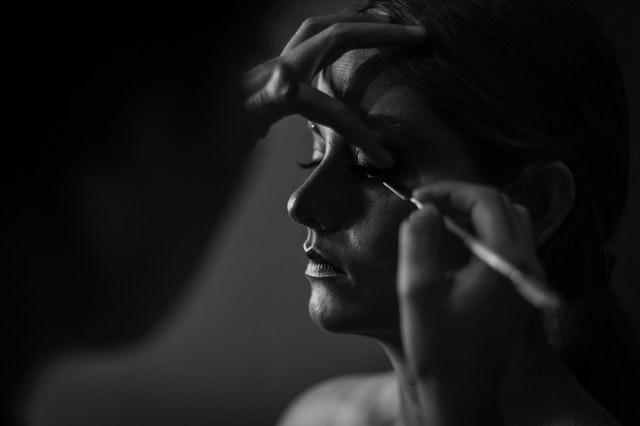 ciemne zdjęcie kobiety, której ktoś maluje twarz