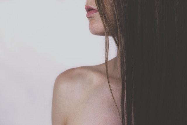 kobieta z długimi włosami stoi bokiem bez koszulki