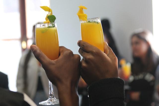 dwie filiżanki z sokiem pomarańczowym w dłoniach