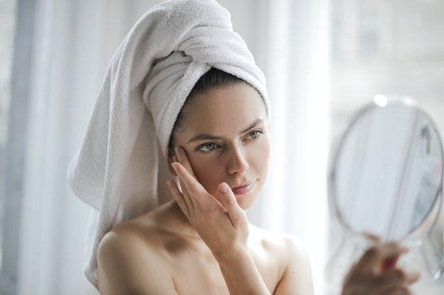 kobieta z białym ręcznikiem na głowie wsmarowuje w twarz krem