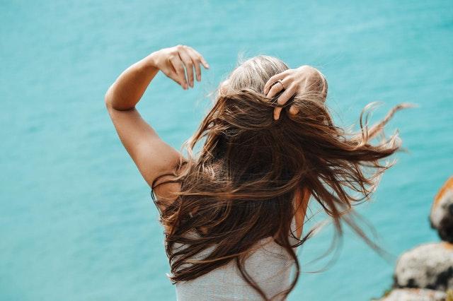 kobieta z długimi włosami stoi tyłem a wiatr rozwiewa jej włosy