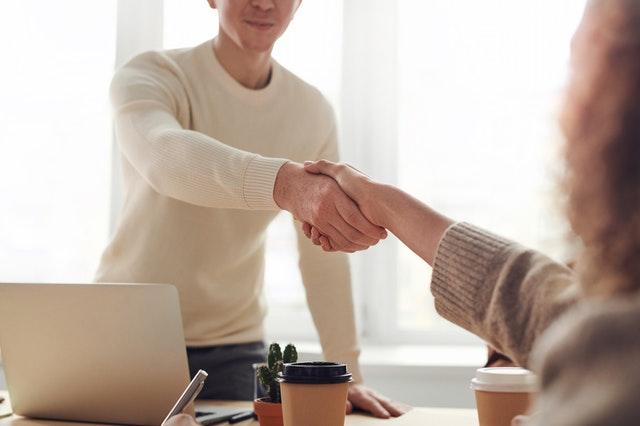 mężczyzna w białym swetrze podaje rękę nad stołem