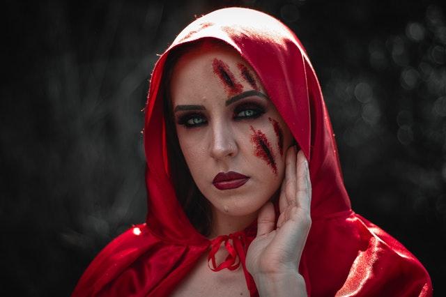 kobieta patrzy w obiektyw z czerwoną sztuczną blizną na twarzy