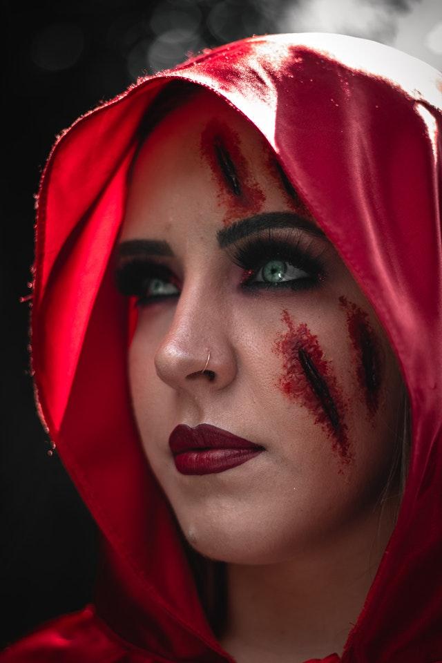 kobieta w czerwonym kapturze ze sztuczną blizną na policzku