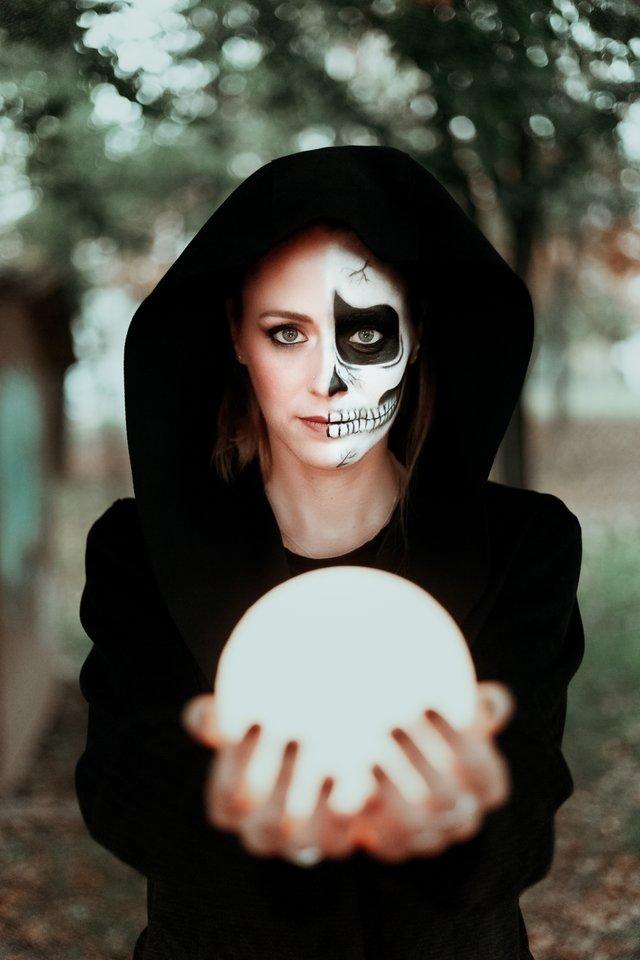 kobieta z połową umalowanej twarzy trzyma w dłoniach białą kulę