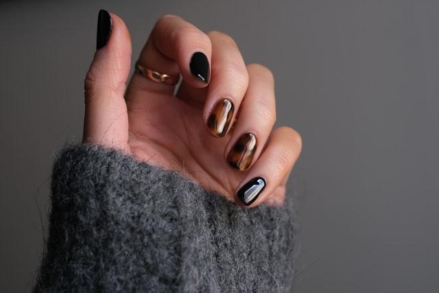 zdjęcie dłoni z paznokciami czarnymi i w panterkę