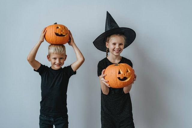 dzieci ubrane na czarno trzymające dynie