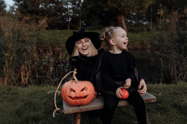 dziewczynka z mamą w ciemnych ubraniach pozują na ławeczce