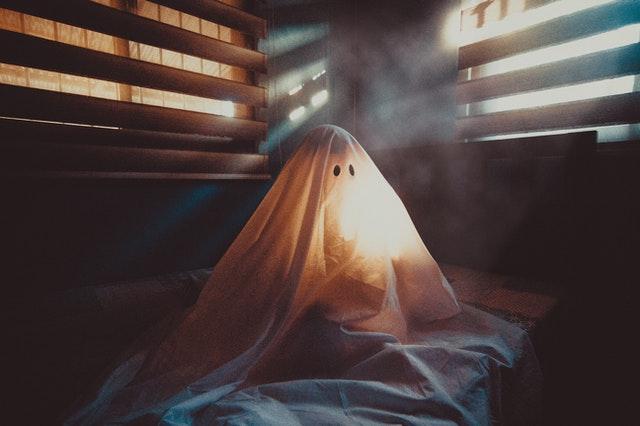 dziecko przebrane za ducha siedzi na łóżku w ciemnym pokoju z żaluzjami