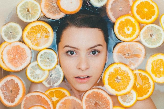 brunetka w delikatnym makijażu zanurzona w wodzie z plastrami pomarańczy