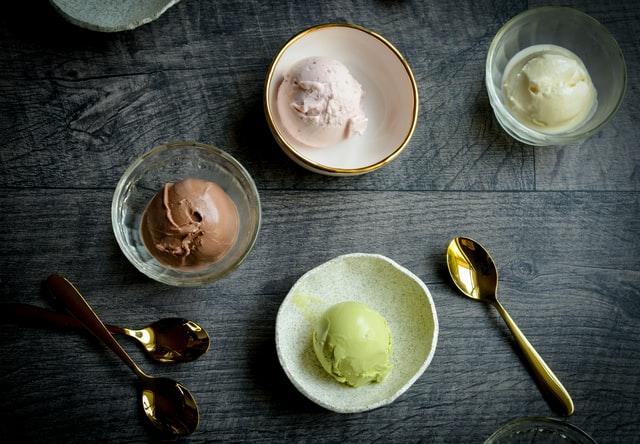 lody o kolorze brązowym, zielonym i beżowym w miseczkach na czarnym stole