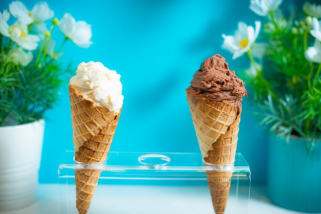 dwa lody w rożku na niebieskim tle
