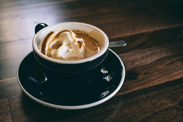 lody śmietankowe w filiżance z kawą stoi na stole