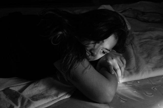 czarno białe zdjęcie dziewczyny leżącej w rozpuszczonych włosach na łóżku