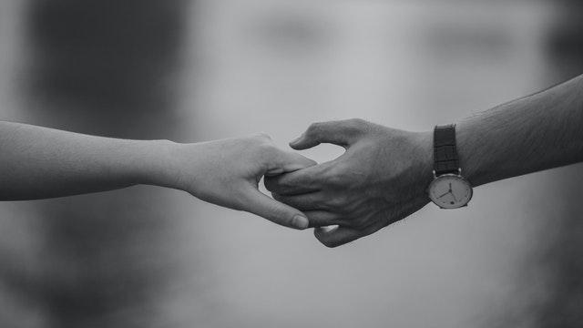 czarno-białe zdjęcie dwóch dłoni, które się ze sobą trzymają