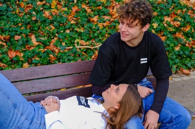 dziewczyna z długimi włosami leży na ławce i trzyma głowę na chłopaku