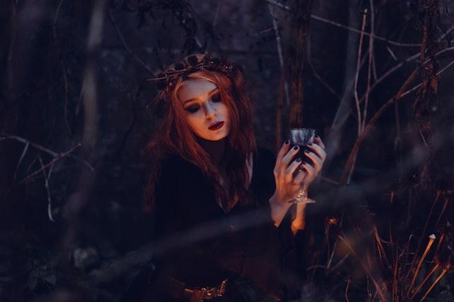 rudowłosa kobieta w mocnym makijażu siedzi w lesie nocą