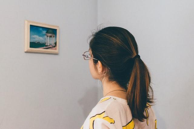 brunetka w spiętych włosach wpatruje się w mały obraz na białej ścianie