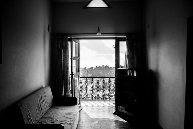 czarno białe zdjęcie mieszkania z otwartym szeroko oknem i kanapą