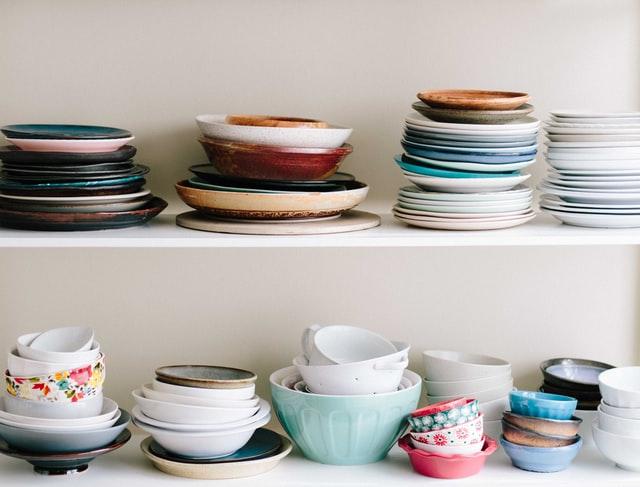 kolorowe talerze i filiżanki stojące na białych półkach