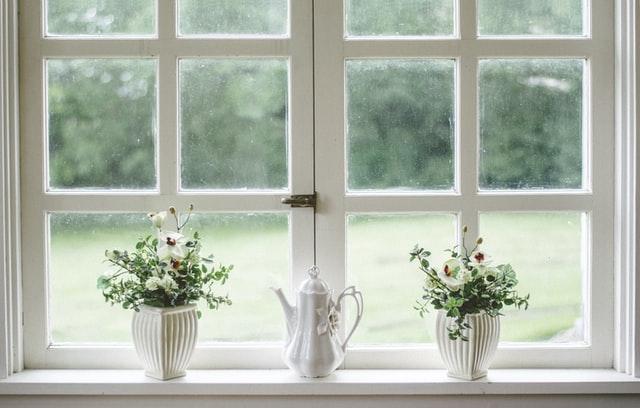 białe wazony z zielonymi kwiatami stojące w oknie na tle zielonego ogrodu
