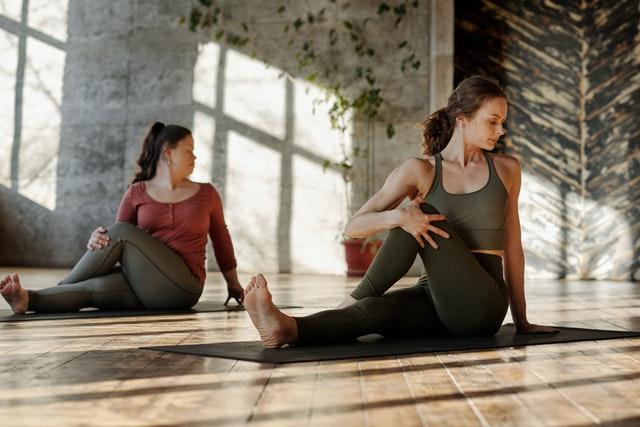 dwie młode kobiety ćwiczą w sali na podłodze siedząc na matach