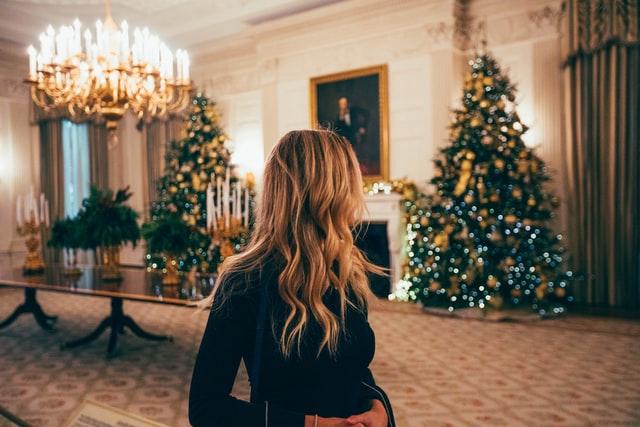 blondynka z długimi włosami zasłania twarz stojąc na tle dwóch dużych choinek w salonie