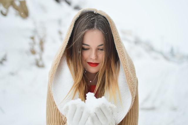 kobieta o czerwonych ustach stoi w kapturze w zimowej scenerii