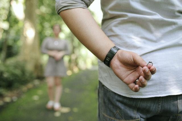 stojący tyłem mężczyzna trzyma w dłoni za plecami pierścionek a przed nim stoi kobieta