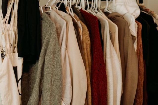 kilka ubrań w kolorach ziemi wiszące na wieszakach