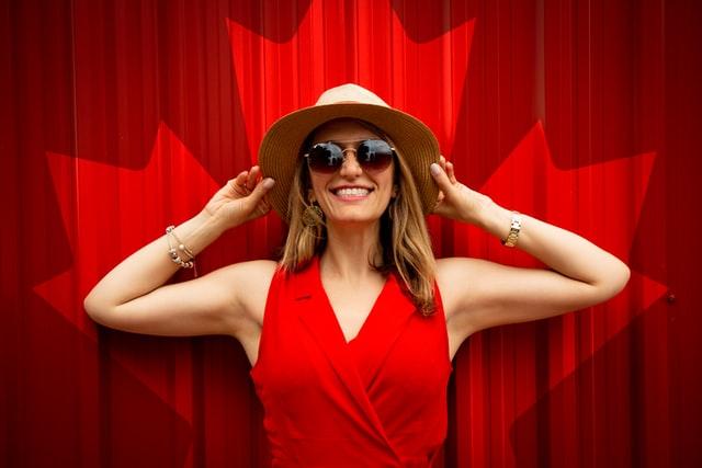 uśmiechnięta blondynka w kapeluszu i okularach przeciwsłonecznych na tle czerwonej ściany