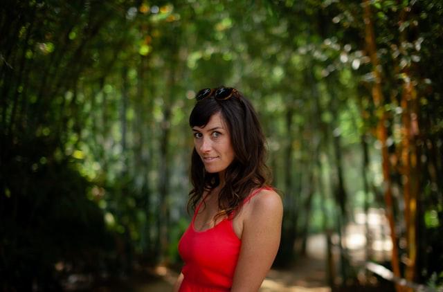 brunetka w rozpuszczonych włosach i czerwonej sukience na tle zielonego lasu
