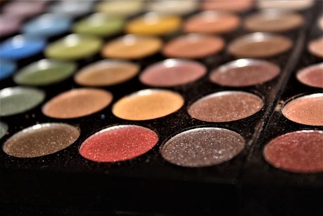 zbliżenie na kolorowe cienie do makijażu w czarnej paletce