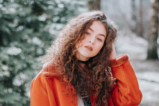 dziewczyna z długimi rozpuszczonymi włosami trzyma się za głowę i pozuje w pomarańczowej kurtce