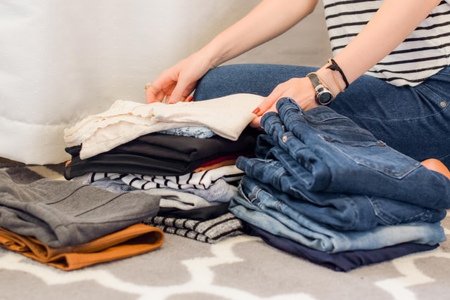 kobiece ręce układają koszulki i dżinsy na łóżku