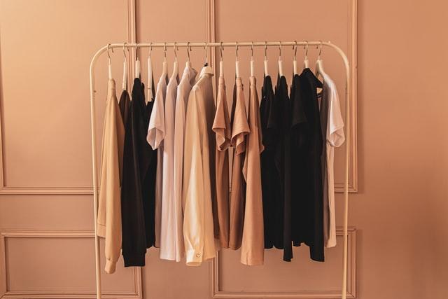 czarne, beżowe i białe koszulki powieszone na wieszaku na tle kremowej ściany