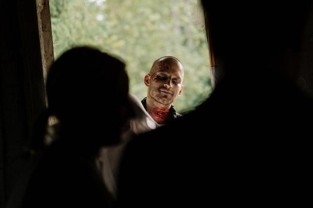 przez okno widać mężczyznę w przebraniu zombie