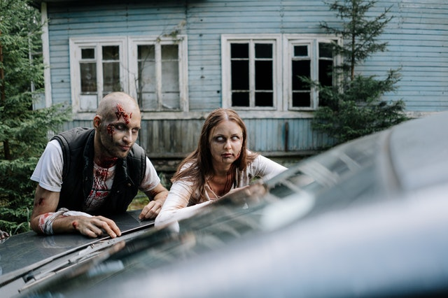 ludzie przebrani za zombie opierają się o auto