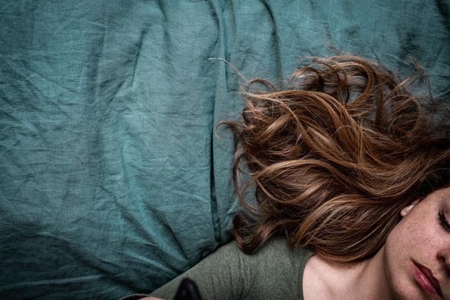 kobieta leżąca na niebieskiej pościeli z rozpuszczonymi włosami