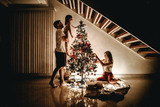 czteroosobowa rodzina stoi w salonie w oddali przy oświetlonej choince