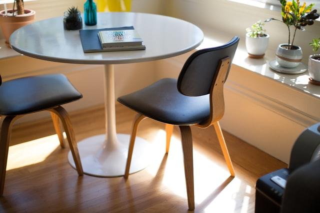 szare krzesła stojące przy okrągłym stole w oświetlonym pomieszczeniu