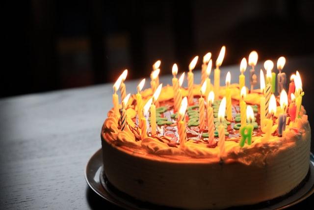 tort w ciepłych barwach z palącymi się na nim świeczkami