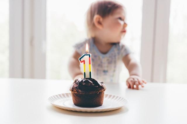 małe dziecko stojące przy stole. na którym stoi brązowe ciasteczko z cyfrą jeden wbitą w nie