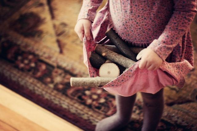mała dziewczynka ubrana w różową spódniczkę, w której trzyma drewno