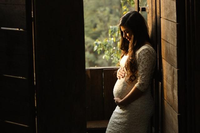ciężarna kobieta z długimi włosami oparta o ścianę na tle otwartego okna