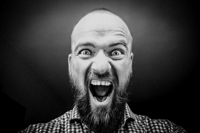czarno białe zdjęcie łysego mężczyzny z brodą, ,który krzyczy